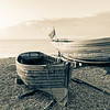Two varnished clinker boats pulled up on beach