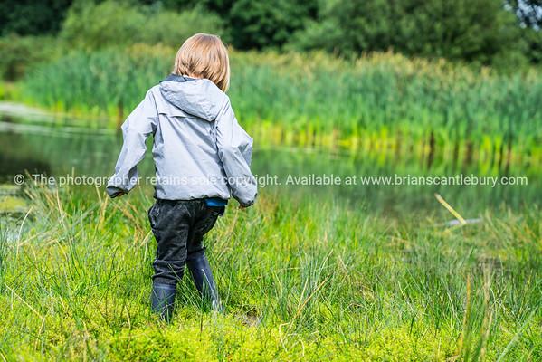 Boy plays on edge of swampy pond
