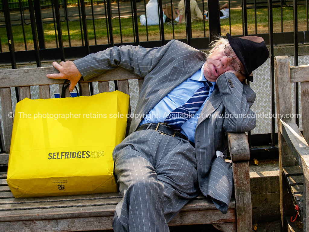 """Gentleman, sleeping on bench, with yellow Selfridges shopping bag. Photograph. A view of the UK<br /> Model released; no, for editorial & personal use. SEE ALSO:   <a href=""""http://www.blurb.com/b/893070-impressions-of-the-uk"""">http://www.blurb.com/b/893070-impressions-of-the-uk</a>"""