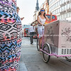 Ice cream cart pedaled along sidewalk past people.