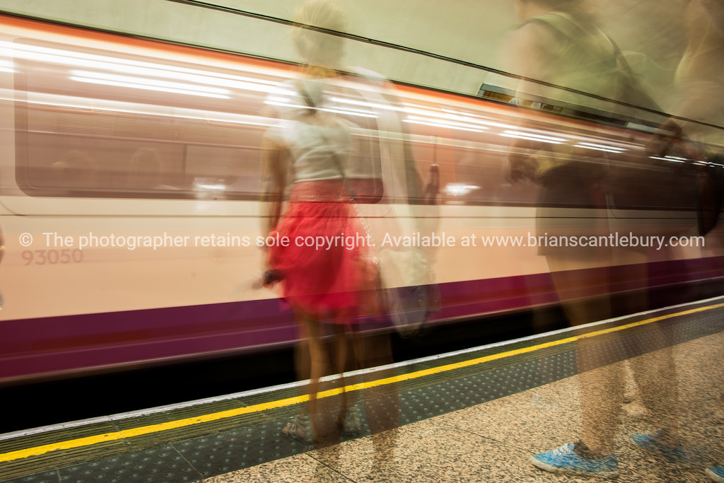 Blurred images of waiting commuters and train moving in station