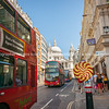 London street scene with doubledecker buses passing giant lollypop as people walk by.
