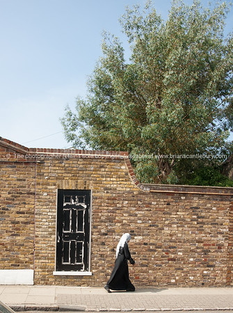 Muslim woman in black and white passes a brick wall with black and white door.