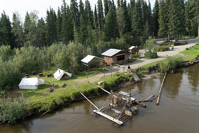 Native fishing village with salmon wheel floating just off shore