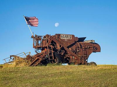 Flag flying, moon over combine