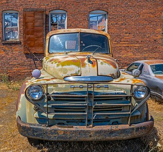 Old car in front of abandoned warehouse