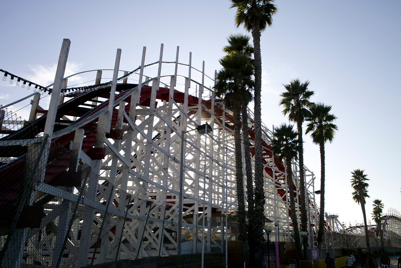 A view of an old wood roller coaster partially silhouetted by the sun.