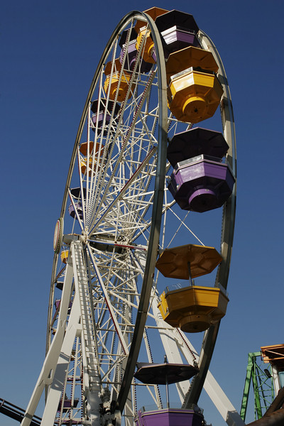 A ferris wheel with multi-colored cars in an amusement park. This view from underneath emphasizes the height.
