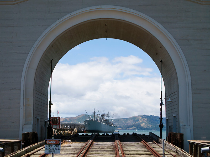 A view of the Jeremiah O'Brian liberty ship and the Marin Headlands. The archway and the rails in the foreground serve as a launch for boats into San Francisco harbor.