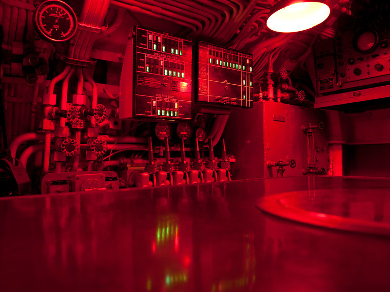 The command center of a WWII submarine illuminated with red lights to enable clear vision at night or day while running underwater.
