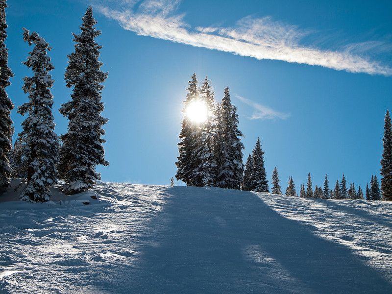 A view looking uphill at a ski slope at a Colorado mountain resort on a clear winter day.