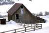 An old barn with a split-rail wood fence meandering to it. The weathered old wood is grayish with age but has successfully withstoood considerable time.