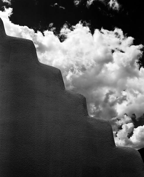 A portion of an adobe wall at the San Geronimo Church in Taos, New Mexico shows a stepped outline against a cloudy sky.