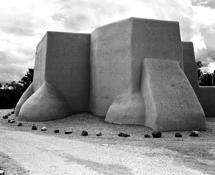 The back side of the San Francisco de Asis church. Built of mud and straw, this traditional adobe-style church with enormous foundations is a landmark in Ranchos de Taos, New Mexico. (Scanned from black and white film.)