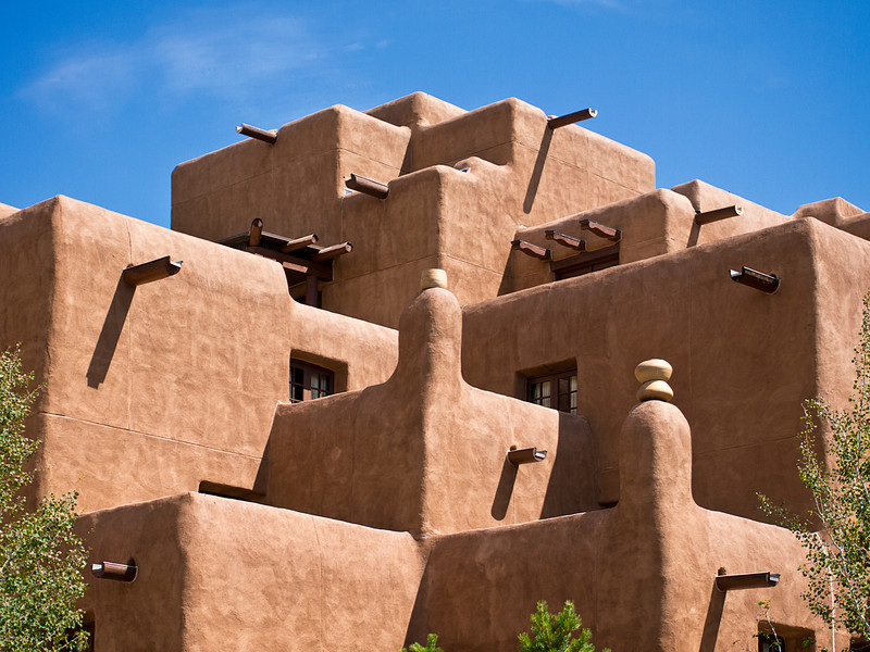 The facade of a hotel built to look like an old native American pueblo with adobe walls, square corners, exposed beams, and more.