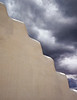 Contrast between a white adobe wall and dark storm clouds in the background. Can be used as a symbol of calm and turmoil.