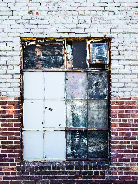 A boarded up window with broken panes is common with old brick warehouses in areas of urban decay.