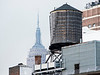 On a hazy day in New York, The Empire State Building rises in over a classic wooden water tower on the roof of a building.
