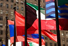 A number of bright and colorful flags, waving wildly in the wind, on a sunny day at the flag pavilion at Rockefeller Center in New York City.