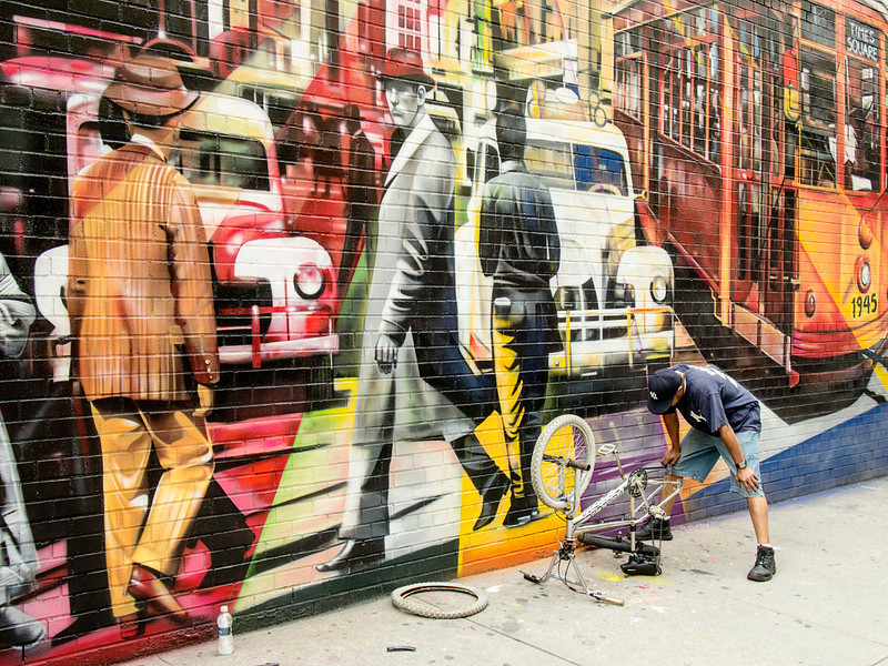 A bicycle repairman on a sidewalk near the High Line Park blends into a wall mural depicting New York City in the middle of the 20th century.