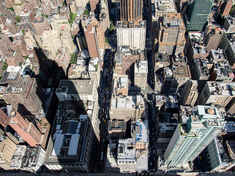 On a sunny day, the shadow of the Empire State building extends over blocks of buildings throughout midtown Manhattan in New York City.