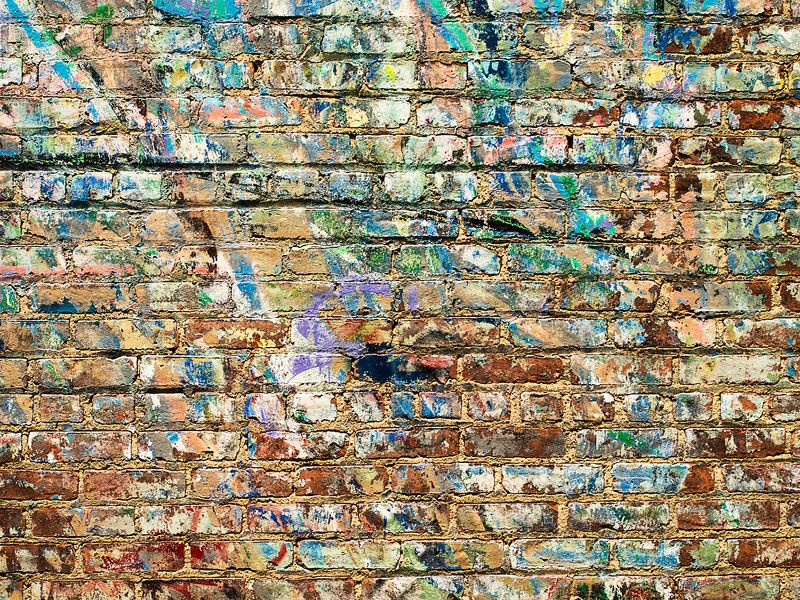 A background image of paint splattered on a brick wall in New York City near the High Line Park.