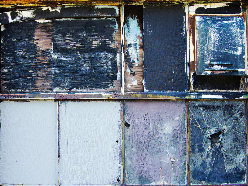 A window on the outside of an old warehouse where the various window panes have been broken and covered up with different fragments of wood forming an unusual texture of urban decay.