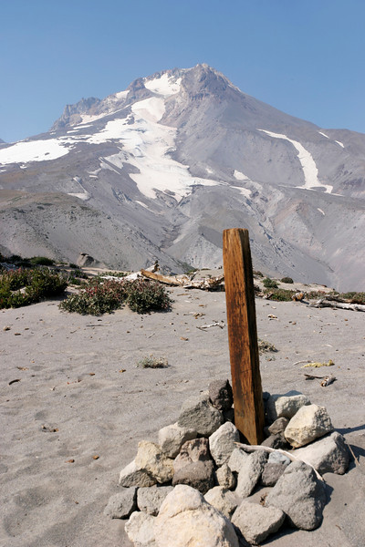 A wood post marking a hiking trail with the summit of Mt. Hood in the background. This area of Mt. Hood is composed of loose volcanic ash and sand.