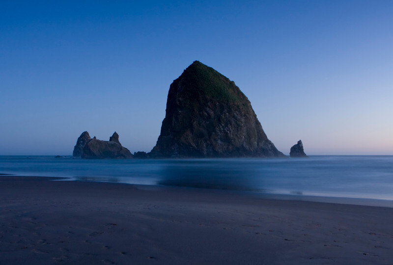A view of Haystock Rock just after sundown. The sun has gone down over the horizon and has left just enough light for a deep blue sky. Haystack Rock, located at Cannon Beach in Oregon, is one of the largest sea stacks on the west Coast of the United States and is over 200 feet tall.
