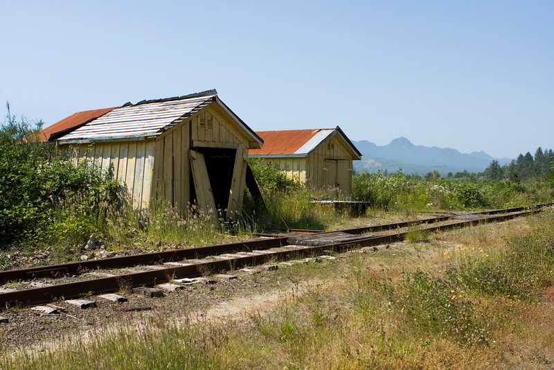 A couple of old railroad buildings, maybe an old station, located in a small town on the Oregon Coast. The old maintenance sheds are apparently not used and are in poor condition.