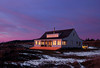 The main house at Pile Point at dusk with the last flash of light from the sun reflecting off the windows.