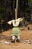 A scarecrow in the shape of a woman. Fully clothed, with a dress and blouse, this scarecrow is attached to a post at the edge of a garden. Traditionally, on farms, these creations are expected to scare off crows and other birds.