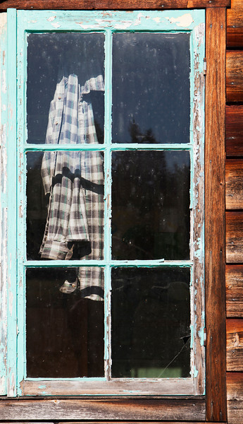 An old plaid work shirt hanging behind an old shed window with peeling and crackled turquoise paint.