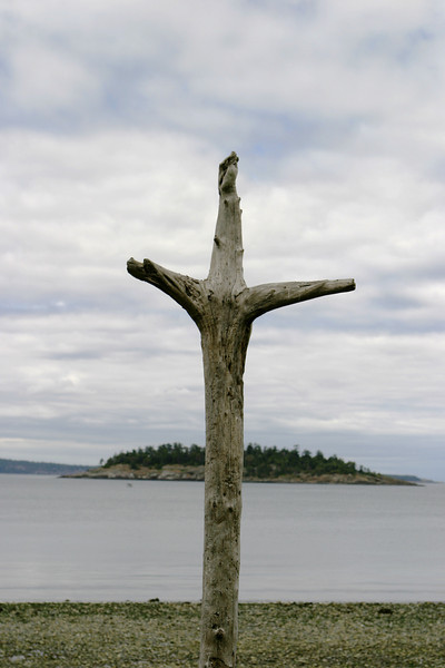 A natural wood cross, made of driftwood, that is standing on a beach in the Pacific Northwest.