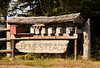 A cluster of mailboxes on a rural postal route. The Homestead sign carved into driftwood provides a touch of country.