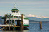 A ferry boat tied up at dock with the snow covered Mt. Baker in the background.