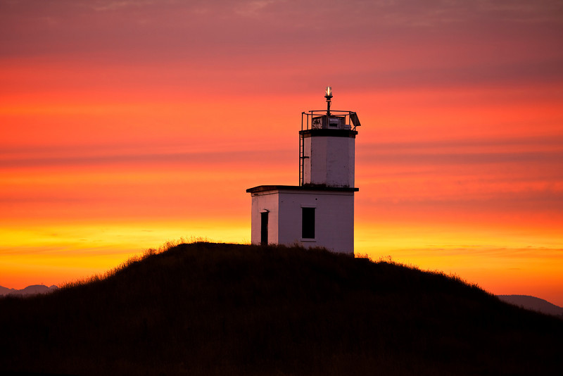 The first light of dawn greets the Cattle Point lighthouse with a glowing rainbow of color spreading across the morning sky.The signal light itself is still glowing.