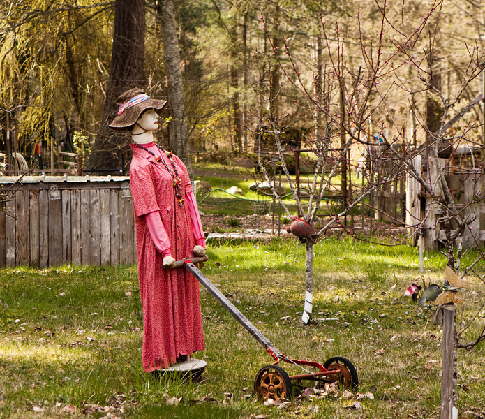 A female scarecrow pushing a lawnmower is dressed in a red polka-dot dress with a hat.