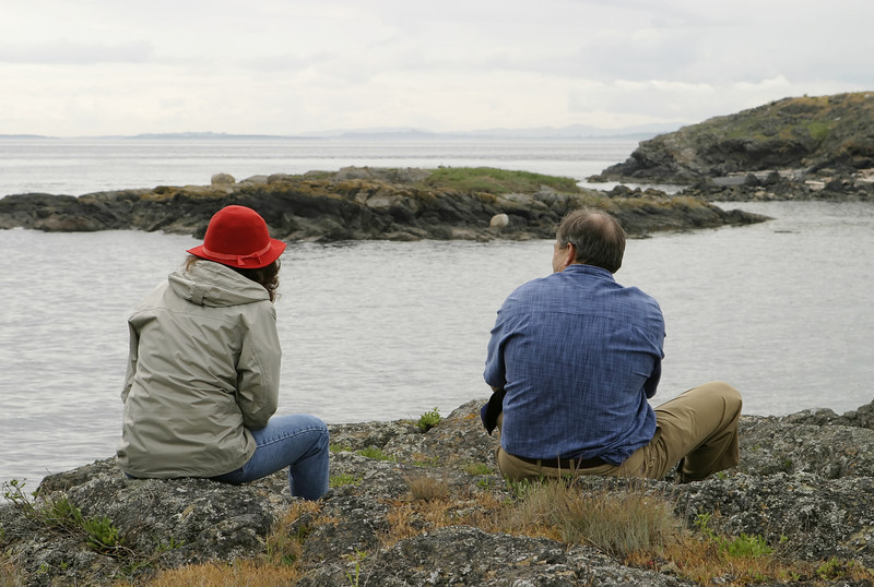A woman in a red hat and a man in blue shirt are relaxing while sitting on some rocks and looking out over Haro Strait.