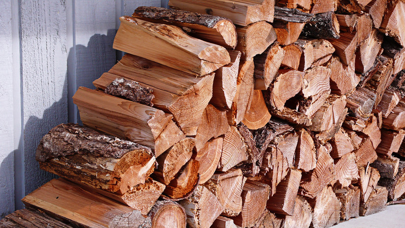 A pile of split firewood neatly stacked and organized in front of a shed.