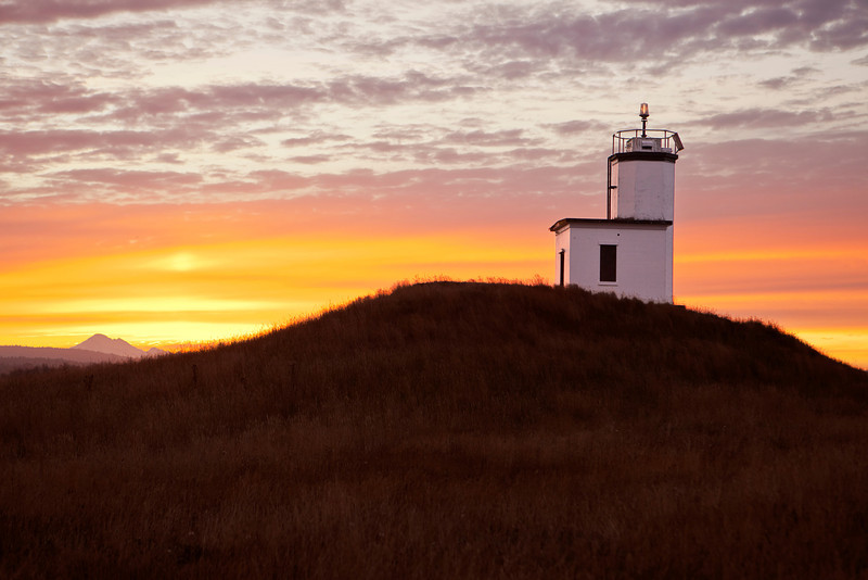 The lighthouse at Cattle Point on San Juan Island stands on a small hill and, at sunrise, the white walls start to glow. In the background, Mt. Baker is just visible along the horizon.
