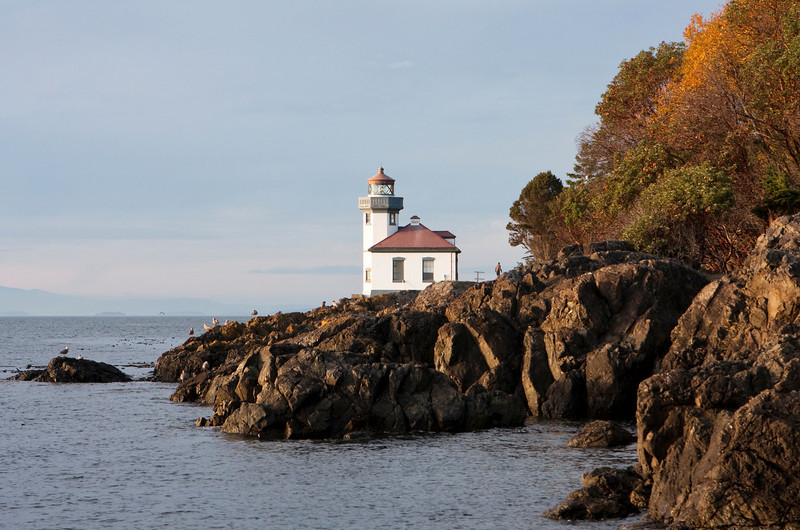 Lime Kiln lighthouse, surrounded by the rocky coastline, is illuminated by the warm light of a late autumn sunset.