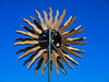 A wood whirlygig in the form of a sun with radiating rays outlined against a bright blue sky.