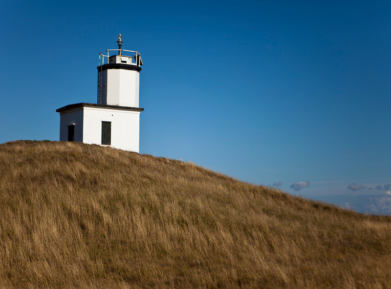 The lighthouse at Cattle Point is a local landmark on San Juan Island in Washington State. The small white structure is at the end of the island on top of a small hummock or hill.