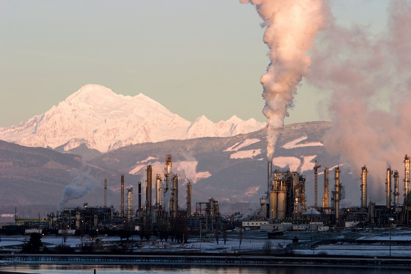 An oil refinery in operation near Mt. Baker in Washington State. This refinery is emitting quantities of steam or other pollutants into the clean air as it converts oil into gasoline and other petroleum products. Taken near sunset, the refinery is ominously in shadow while the mountains and steam are higlighted by the afternoon sun.