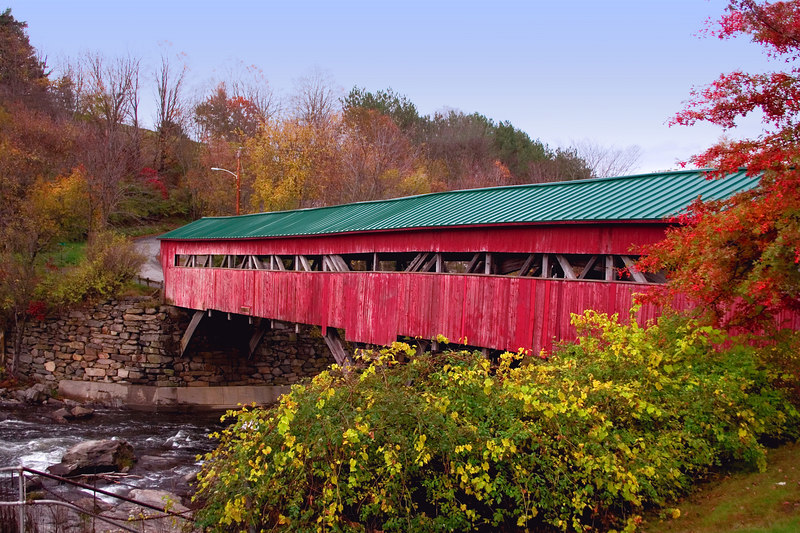 Taftsville Covered Bridge - The water of the Ottauquechee river spills over a dam and passes under the covered bridge.