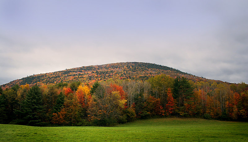 The sun peeks through the clouds to highlight the magnificent fall color and green pastures.