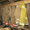 The fire uniforms of the all-volunteer Waldron Island Fire Department hanging up from hooks in a barn that is used for temporary storage.