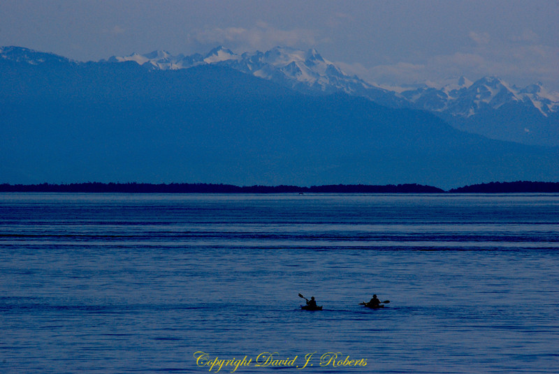 Two kayakers of the west side of San Juan Island, Washington with the Olympic Mountains in the background