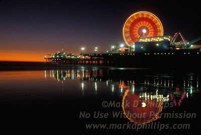 Santa Monica Pier Ferris Wheel spins in the night sky and reflects in the water of the Pacific Ocean.